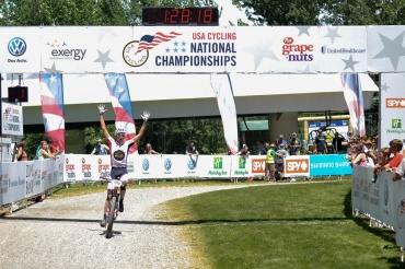 Marcus Segedin raises his arms in the universal symbol for victory as he crosses the finish line to win the USA Cycling national championship cross country race, category 1, age 15-16.