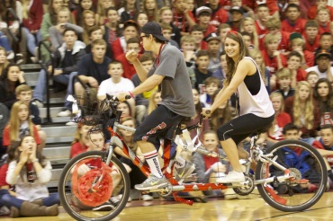Homecoming Court Canditates Douglas Pardella and Celeste Carswell round the gym on a tandem bicycle.