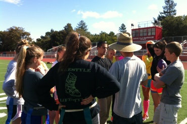 Junior coach Navid Izadjou speaks to his players about the upcoming Powder Puff football game.