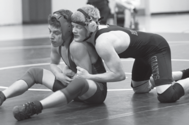 JUNIOR JACK TWOMEY, right, hits the mat during the annual King of the Mountain match against Tam. His win helped Giants wrestlers secure the King of the Mountain plaque for the sixth year in a row.