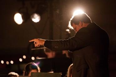 Music teacher John Mattern directs the Symphonic Band under the spotlight.