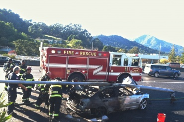 Firefighters work to clear the Silver BMW from the off ramp