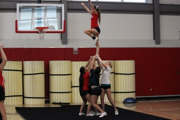 Cheerleaders practice their routine during a practice in the small gym.