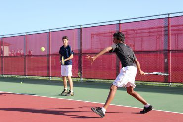 Freshmen  Cengiz Aksu and Dominic Barretto warm up before practice on the Redwood tennis courts.  The two players are third and fourth on the team ladder, respectively.
