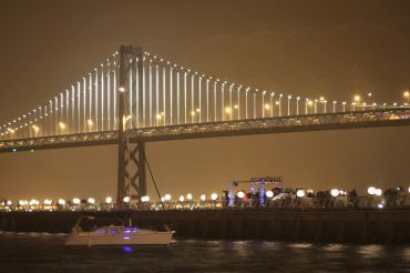 Boats float in front of the Bay lights lighting ceremony.