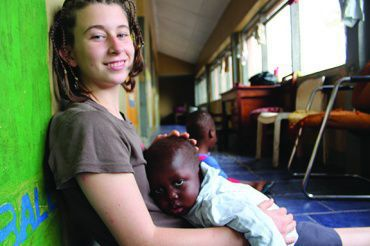 Holding malnourished three-year-old KeKe on her lap, sophomore Kelly McCormish, dedicated her summer to volunteering in an orphanage in Africa