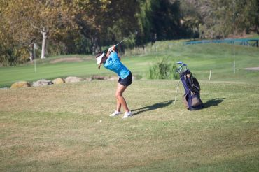 Junior Kendra Loo follows through on her swing during the match at McInnis Park Golf Center against Drake.
