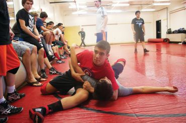 Sparring on the mat against teammate Same Miranda, sophomore Simon Ermolov practices in front of fellow varsity wrestling members. Ermolov placed third in MCALs in the 128-pound weight class last year.