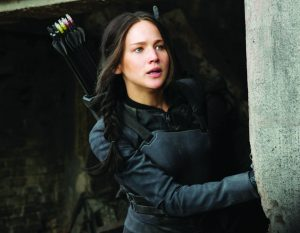 KATNISS EVERDEEN, played by Oscar winning actress Jennifer Lawrence, looks out on District 8 anxiously while visiting a hospital.