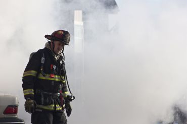 A firefighter walks away from the flames.