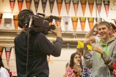 Both the boys' and girls' varsity basketball games were filmed by Comcast Hometown Network at last Friday's game night. Here, sophomore Cody Meylan cheers while a cameraman approaches the crowd.
