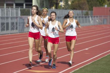 Members of the girls track team run on the Redwood track during a meet against Marin Catholic and Terra Linda. The Giants won the meet.