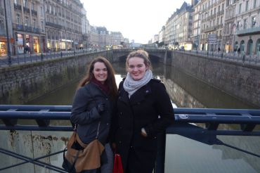 Celebrating New Year's Eve, sisters Taylor and Delaney Benstead overlook the town of Rennes, France from a bridge.