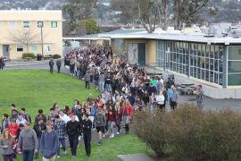 Students walk toward amphitheater after false fire alarm sounds during third period,