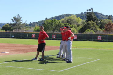 Russo watches practice with the team behind him.