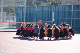 Gathering in a circle, the varsity girls tennis team prepares for the game.