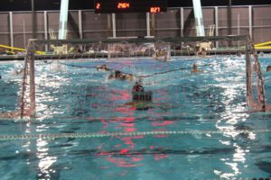 Players swim towards goal.