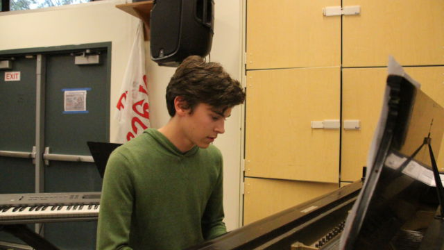 Playing the piano, senior Parker Addison practices the songs within his album while in the Advanced Performance Workshop classroom.