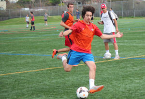 Kicking the ball, junior Lucas Quinto prepares for the season during try-outs.