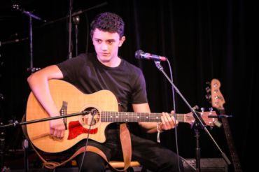 Performing a cover onstage, senior Matty Michna plays his guitar,