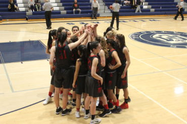 Putting their hands in, the girls' varsity basketball team starts the game off with a loud cheer.