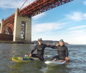 Holding on to his son Zack's shoulder, Cohen rides his board under the Golden Gate Bridge.