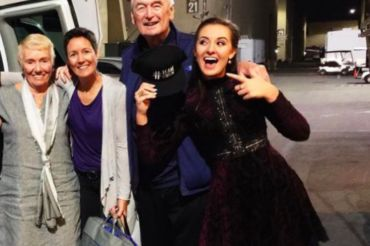 """Holding her """"Team Gwen"""" hat, Caroline Sky stands with her grandparents and mom after the audition."""