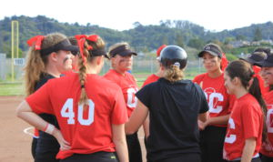 "The team regroups. Junior Cami Klemme wears a small ""GC"" on the ribbon in her hair to honor the late coach Gary Casassa."