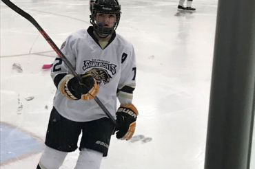GLIDING ACROSS THE ice, freshman Erin McGlynn warms up for a game as a San Francisco Sabercat. McGlynn is a captain for the Sabercats and plays in an all-boy's league.