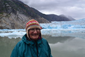Smiling in front of a glacier, Cathy Connors is a professor at the University of Alaska Southeast