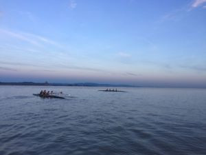 Rowing side by side at practice, the two varsity girls' boats compete in a friendly competition. The team trains every day after school as well as two mornings a week.