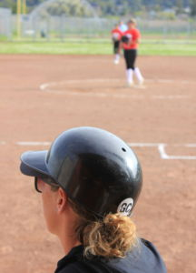 """Head Coach Emily Atkinson wearing a """"GC"""" sticker on her helmet during the game."""
