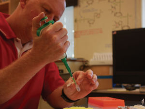 Focusing on the task at hand, Lovelady transfers liquids using a micropipette and other lab equipment