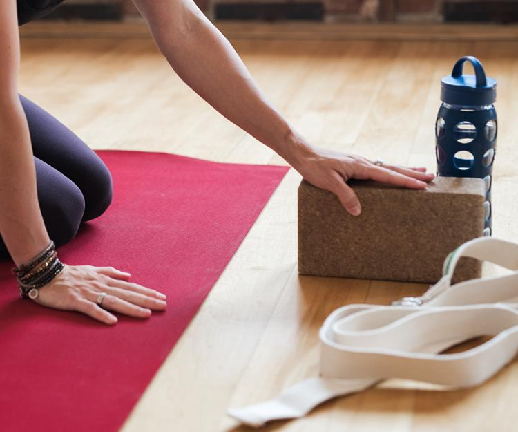 UTILIZING DIFFERENT props to create an effective workout, Yogaworks offers complementary straps, blocks and mats for customers during class.