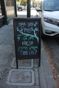 By their storefront, Amphora Nueva advertises fresh olive oil.