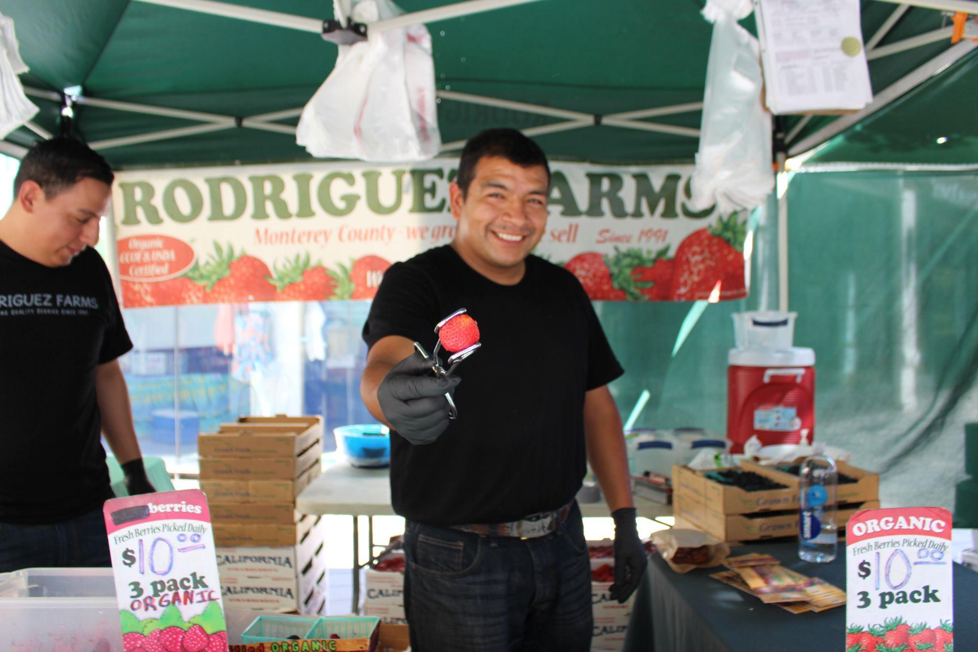Holding out a strawberry, Jose Carpio sells his produce at the Town Center Farmer's Market