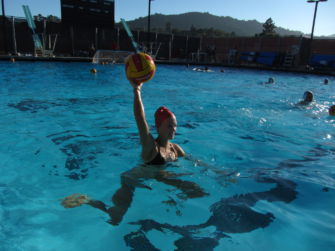 Preparing to pass the ball, sophomore Piper Tonne treads water.