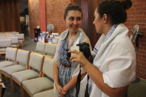 Senior photographers Angelica Vohland (left) and Katie Levy (right) take photos in their local synagogue for 'Women Facing West.'