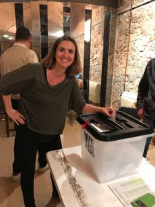Placing her vote, Marta stands next to the ballot box.