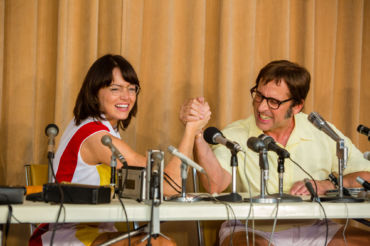 Publicizing their tennis match, Billie Jean King (Emma Stone) and Bobby Riggs (Steve Carell) sit next to each other at a press conference.
