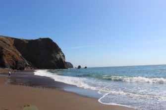 Large, rocky cliffs protrude and surround Tennessee Valley Beach.