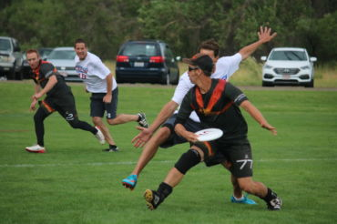 Passing to his teammate, teacher Joe Stewart has been playing ultimate frisbee for 25 years.