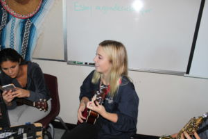 Orrick with a big smile on her face, playing ukulele next to Senior Violet Loo