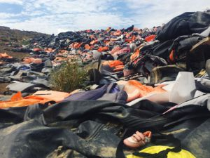 Discarded life jackets are thrown into a growing heap after refugees land on shore.