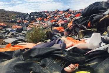 Disregarded life jackets are thrown into a growing heap after refugees land on shore.