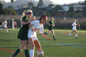 Blocking her competitor out of the way, junior Alexis Nunez defends the ball.