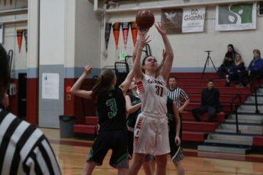 Senior center Julia Guisti rising above defenders for the lay in.