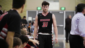 Walking to the bench, junior Scott Matthews high-fives his teammates