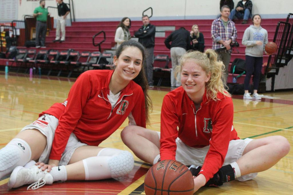 Stretching at Midcourt, senior Zoe Stachowski and junior Jenny Walker prepare fora game.
