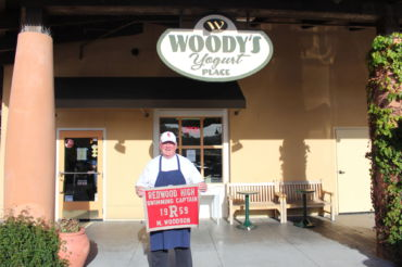 Standing in front of Woody's Yogurt Place, Michael Woodson holds his 1959 varsity swim team captain's flag.